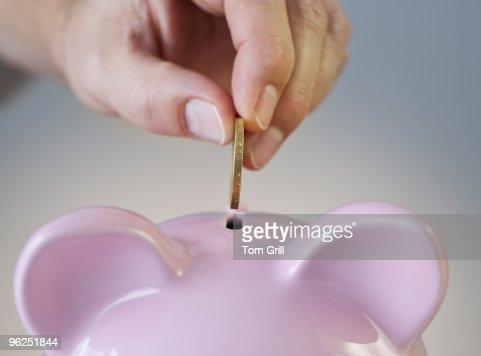 Hand putting British Pound coin in piggy bank : Stock Photo