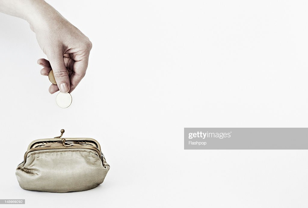 Hand putting coins into a purse
