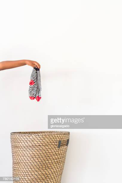 Hand putting dirty socks in laundry basket