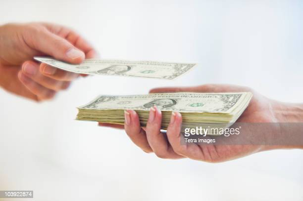 Hand putting dollar bill on top of stack of money