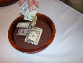 Hand putting money in collection plate