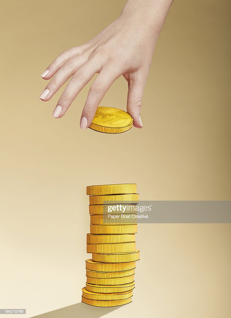 Hand putting paper gold coin on stack of coins : Stock Photo