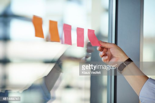 Hand putting Post-It notes on the window