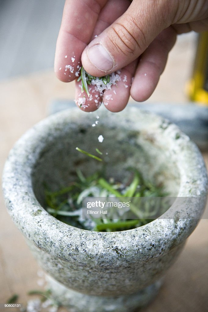 A hand putting salt on rosemary in a mortar Sweden.