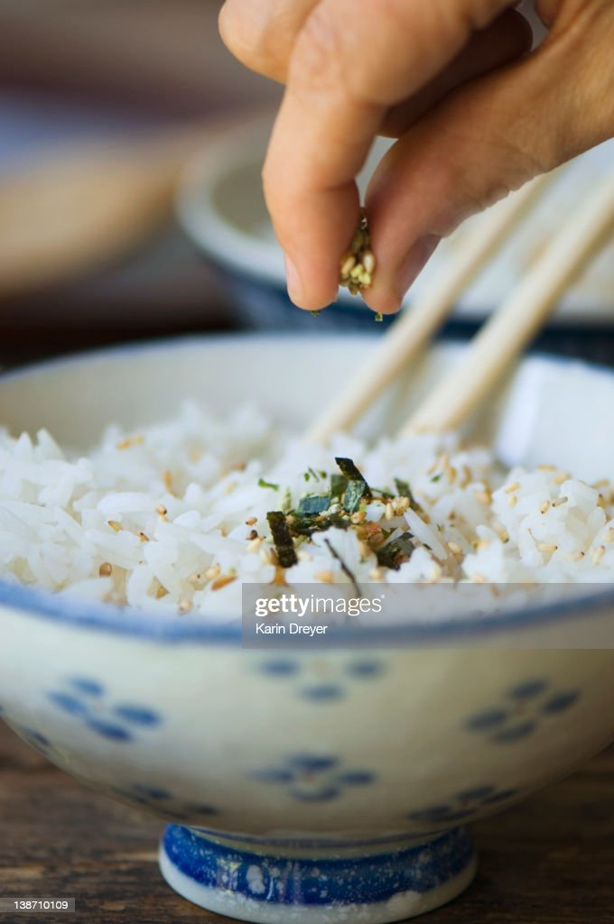 Hand putting seasoning on bowl of rice with chopsticks : Stock Photo