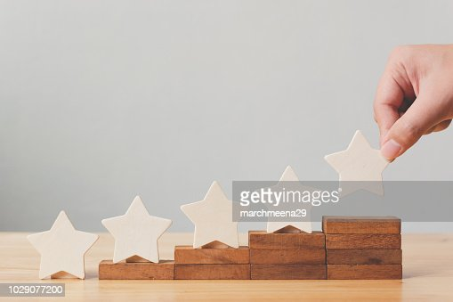 Hand putting wooden five star shape on table. The best excellent business services rating customer experience concept : Stock Photo