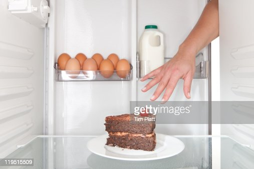 Hand reaches for cake in a fridge. : Stock Photo