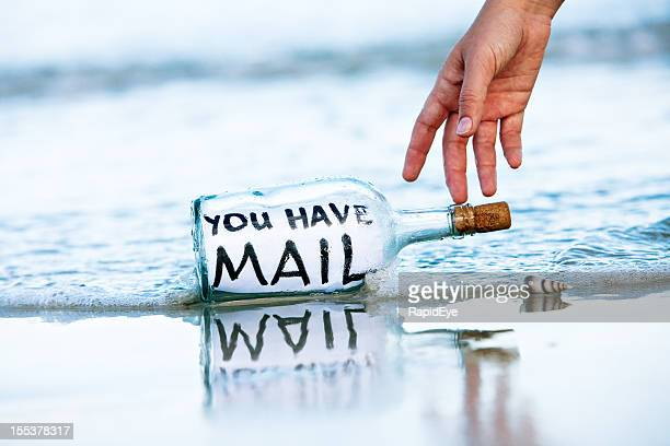 Hand reaches for You have Mail message in bottle