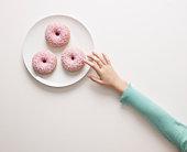 Hand reaching for a doughnut