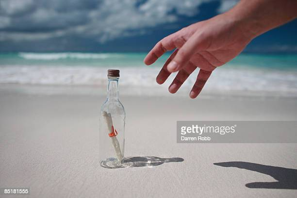 Hand reaching for a message-in-a-bottle on beach