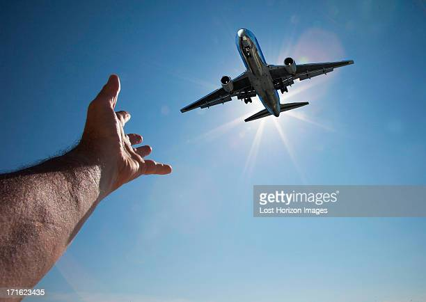 Hand reaching for aeroplane in sky