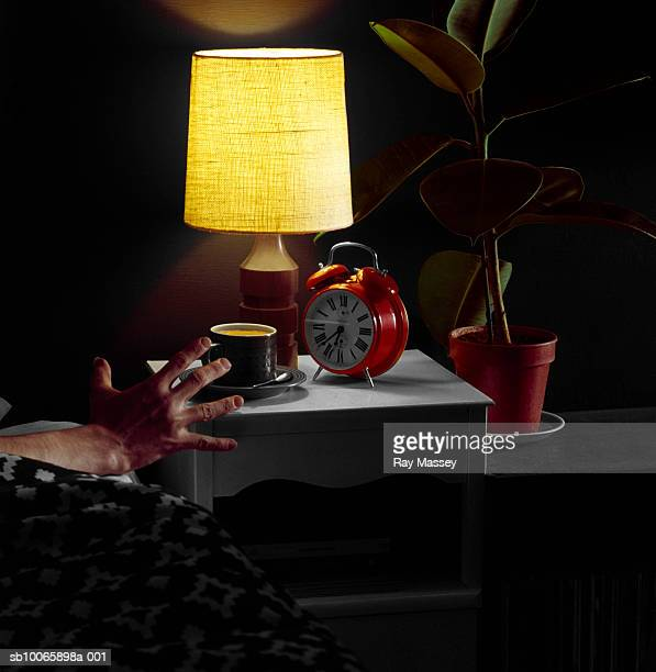 Hand reaching for alarm clock on night table