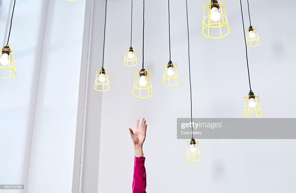 A hand reaching for conceptual idea lightbulbs : Stock Photo