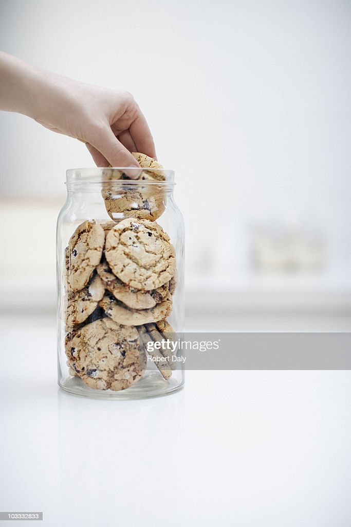 Hand reaching for cookie in jar : Stock Photo