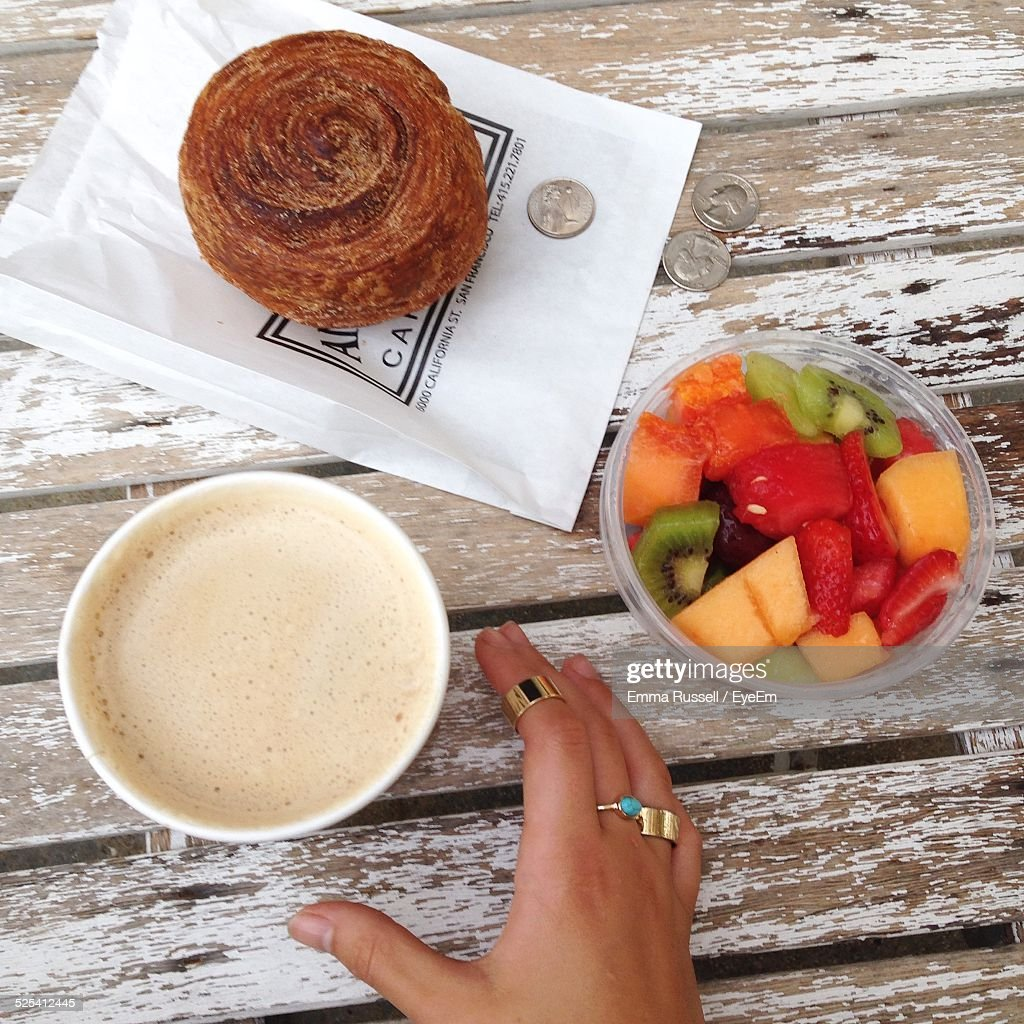 Hand Reaching For Cup Of Coffee On Wooden Table With Bun And Fruit Salad In Plastic Bowl