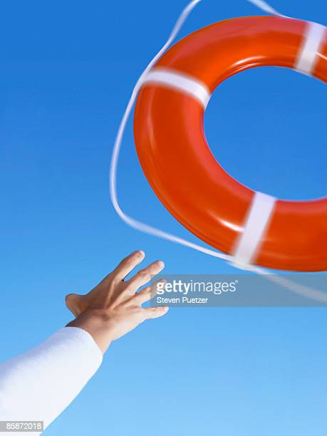 Hand reaching for life ring against blue sky
