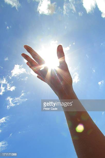 Hand reaching for sun in sky