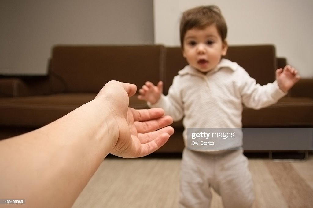 Hand reaching for toddler girl making first steps