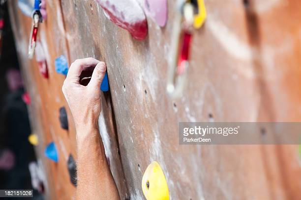 Hand Reaching on Climbing Wall