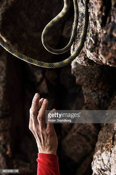Hand reaching out for rope