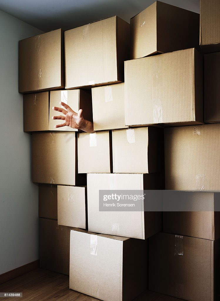 Hand reaching out from behind a wall of boxes. : Stock Photo