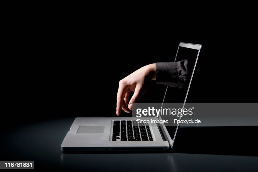 A hand reaching through a laptop to type on the keyboard