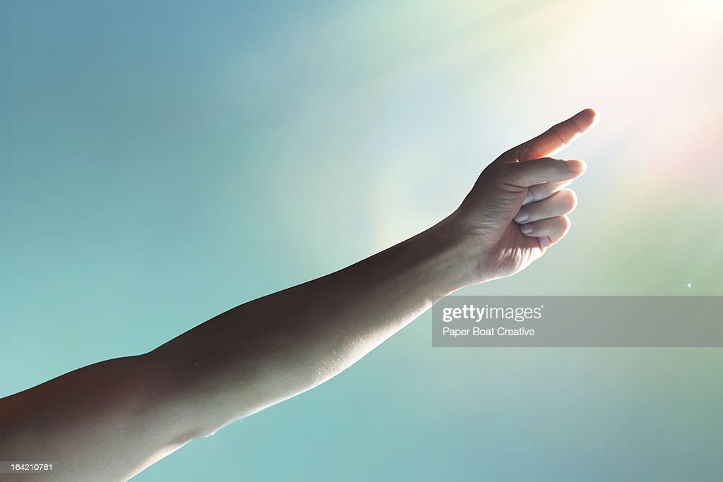 hand reaching to the sky and touching light : Stock Photo
