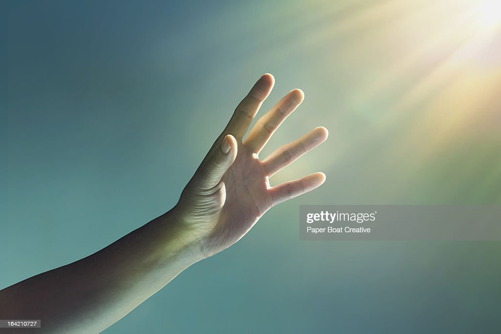 hand reaching towards glowing light from corner : Stock Photo