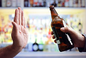 Hand rejecting alcoholic beer beverage concept for alcoholism and addiction