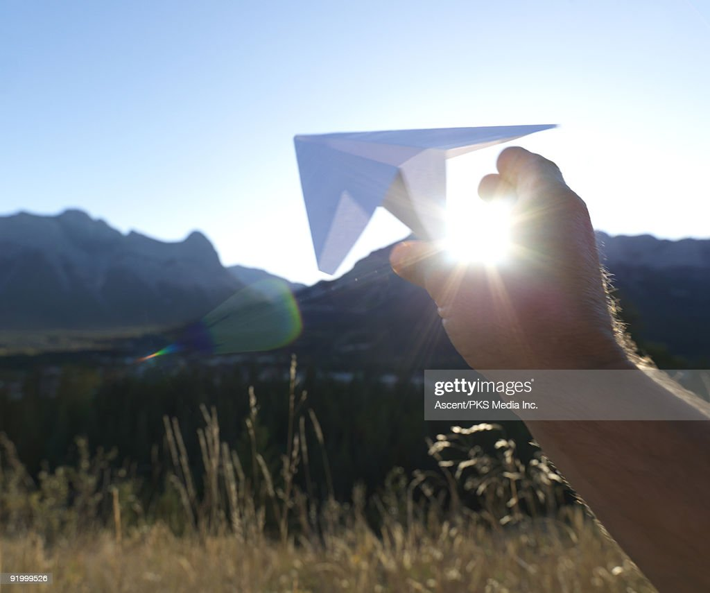 Hand releases paper airplane, above distant mtns
