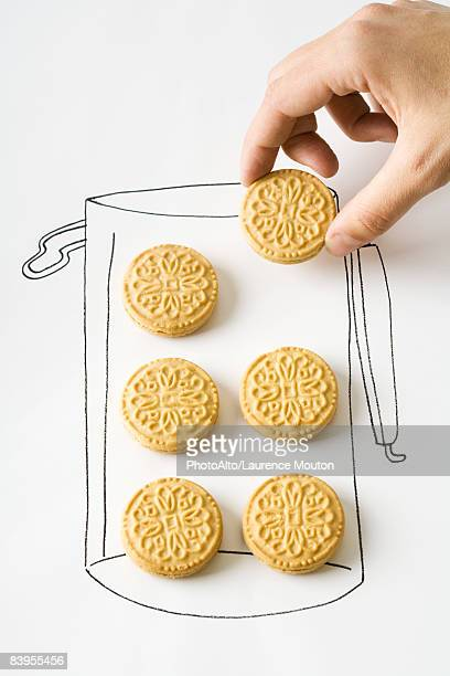 Hand removing cookie from drawing of canister