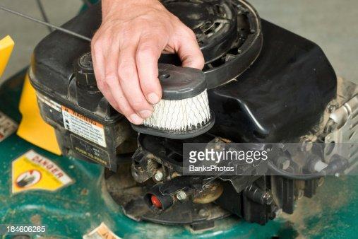 Hand Replacing Lawnmower Air Cleaner