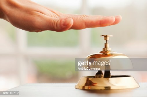Hand ringing service bell on desk beside window