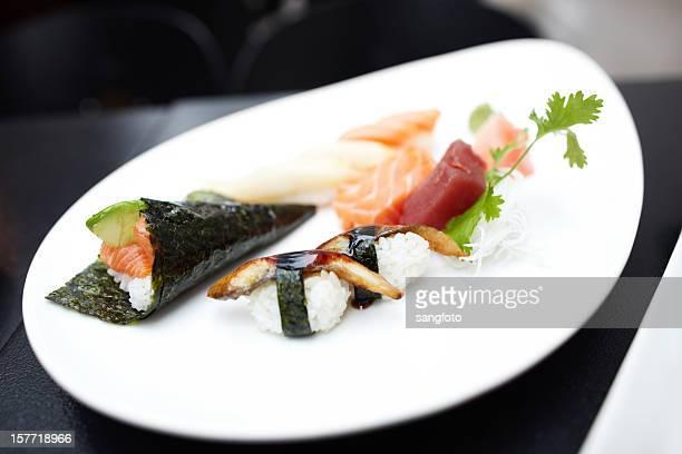 Mão de rolagem e variedade de sashimi em placa