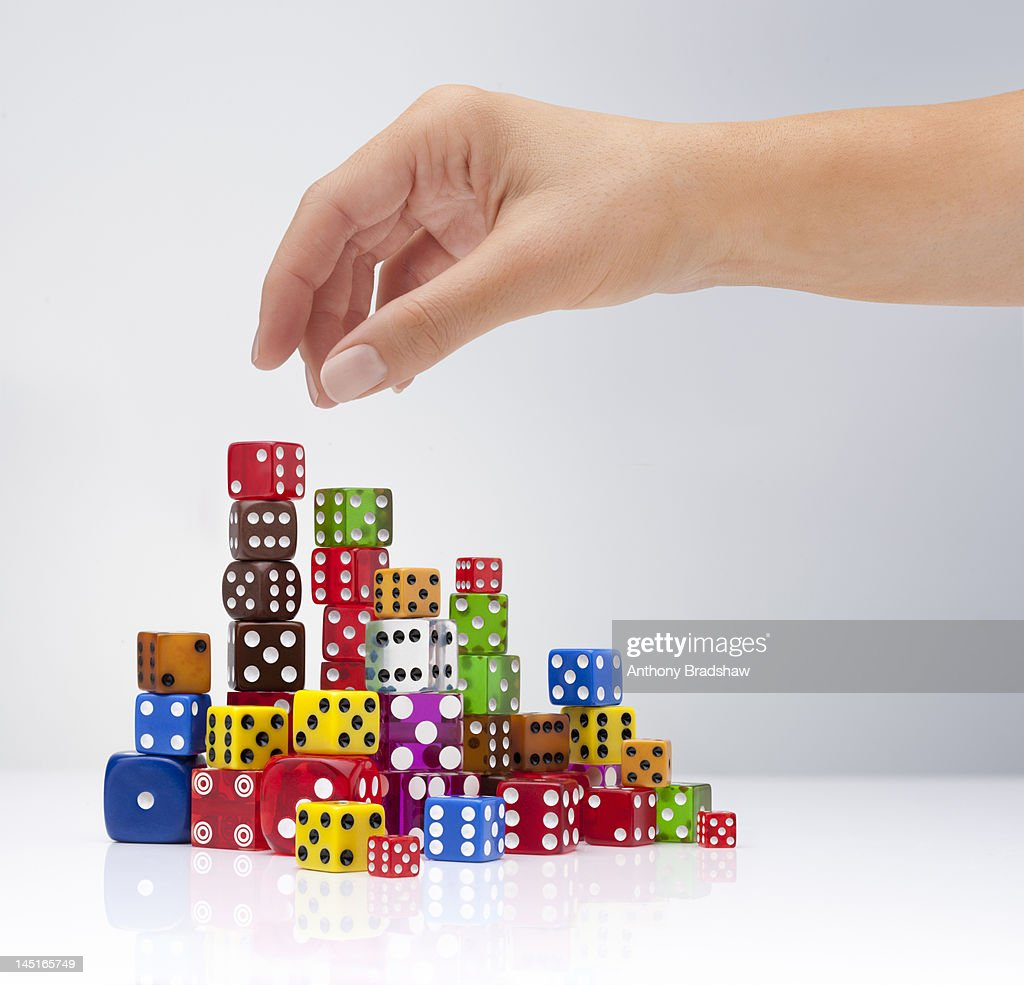 Hand selects a dice : Stock Photo