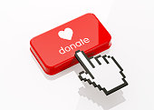 Hand shaped computer cursor is clicking on a red computer button on white reflective surface. Donate writes on button. Horizontal composition with copy space and clipping path.  Donation and charity c