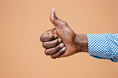 Hand showing OK sign isolated on brown background. Close-up of positive gesture, like, agreement, accept concept concept
