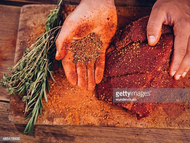Hand mit pikanten Gewürzen mit einem Stück Schweinefleisch mit Schnittkanten