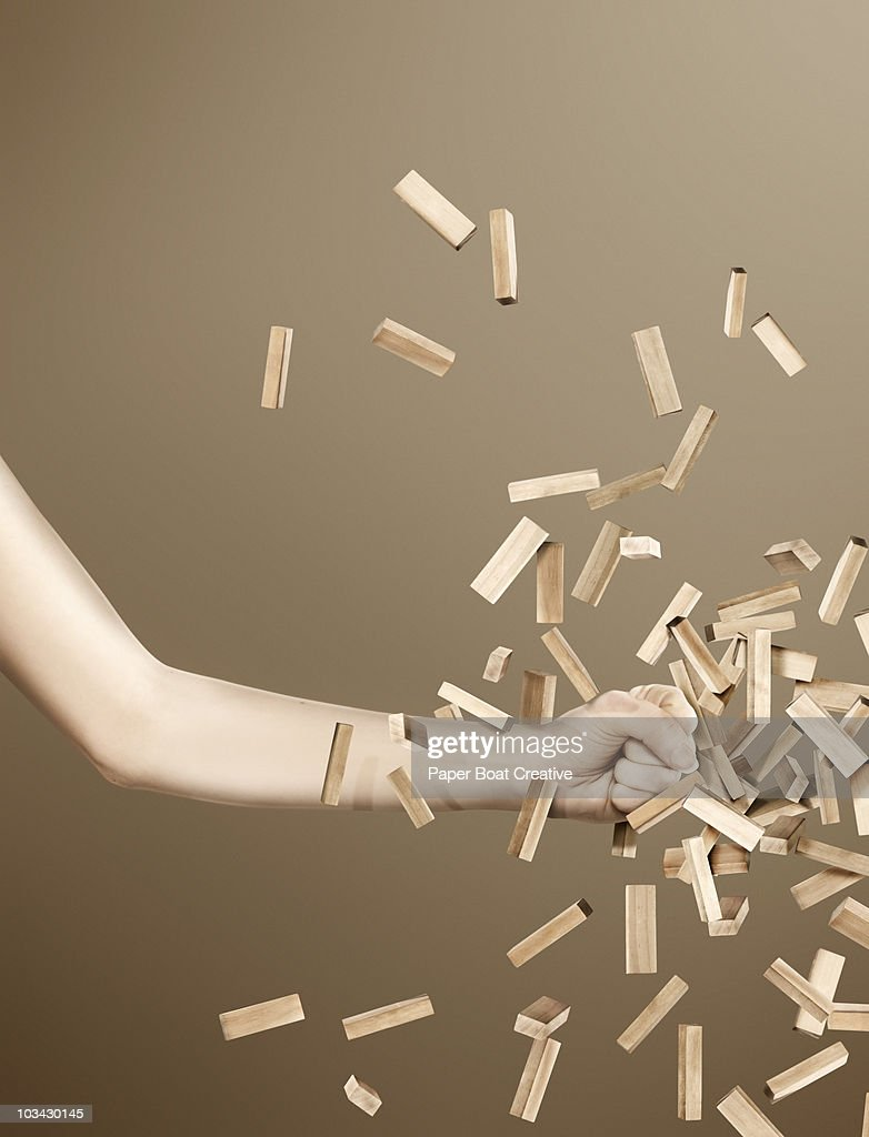 Hand smashing through a pile of wooden blocks