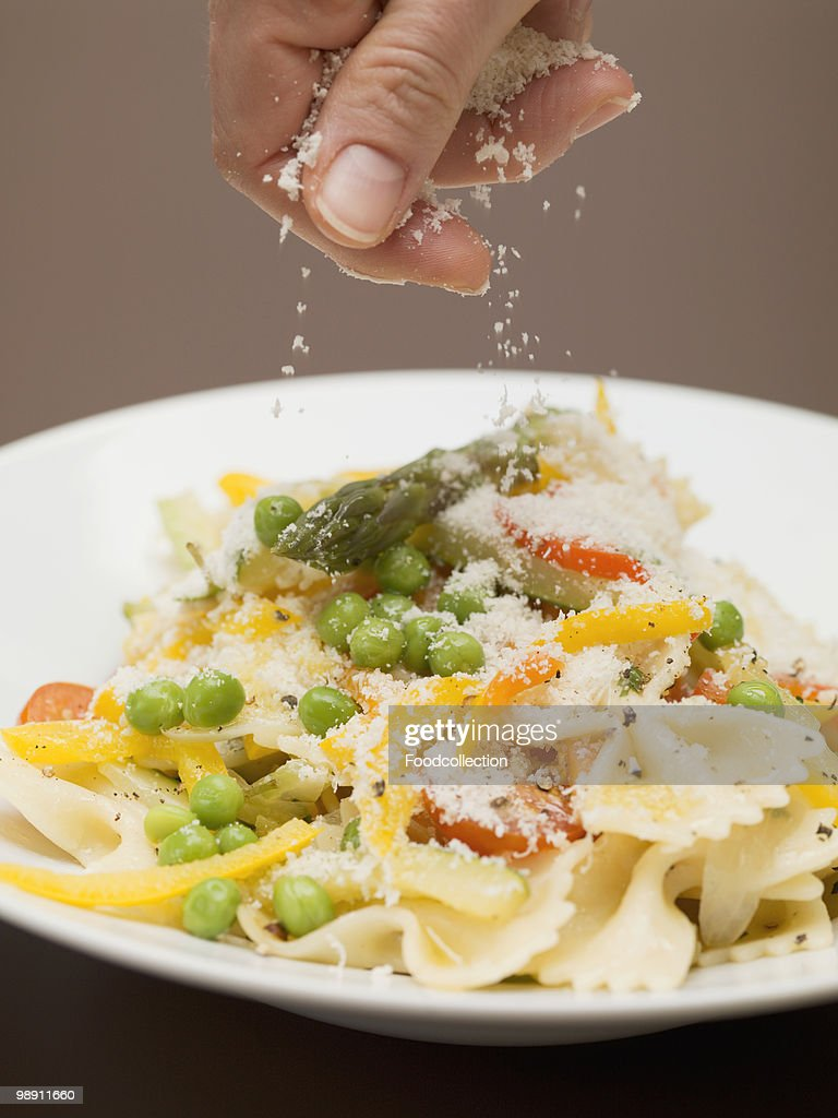 Hand sprinkling cheese on bow tie pasta with vegetables, close-up