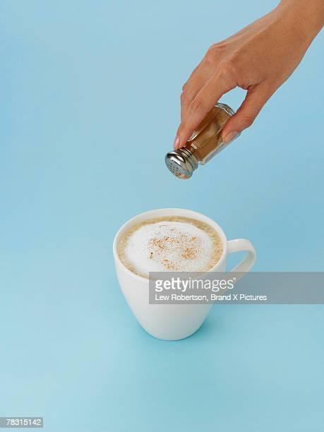 Hand sprinkling cinnamon onto cappuccino