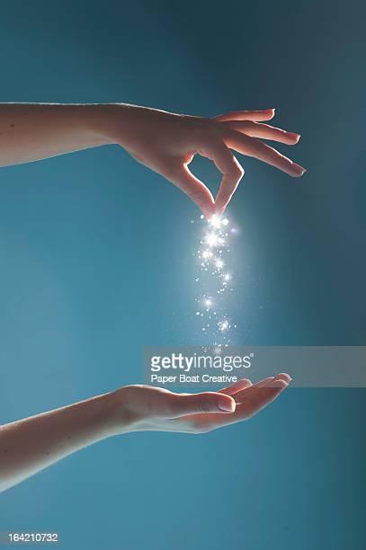 Hand sprinkling light sparkles in studio