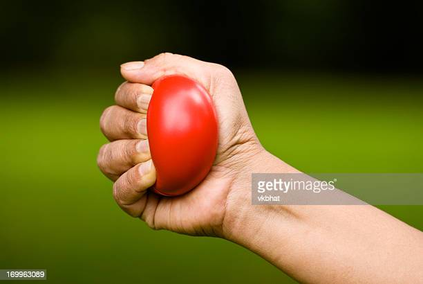 Hand squeezing a red stress ball