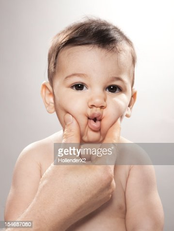 hand squeezing baby's cheeks : Stock Photo
