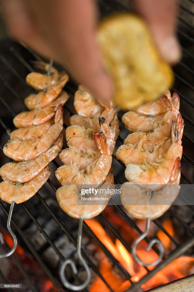 Hand squeezing lemon juice over prawn skewers on grill rack : Stock Photo