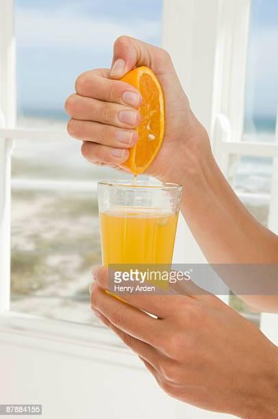 Hand squeezing orange juice