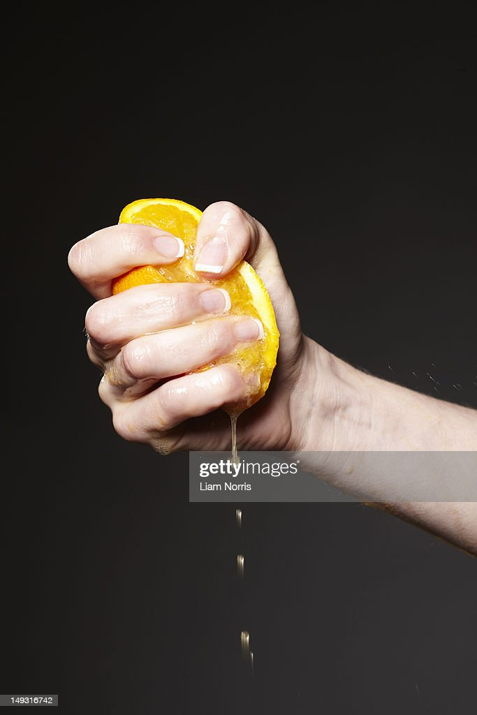 Hand squeezing orange : Stock Photo