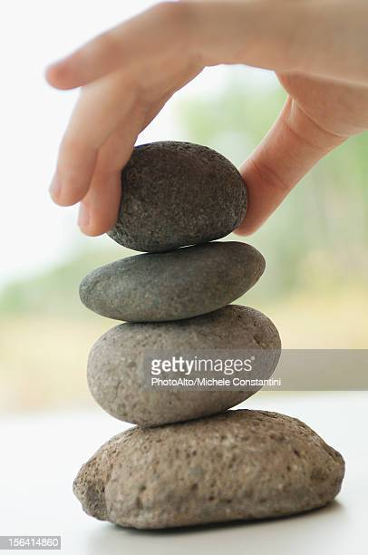 Hand stacking pebbles