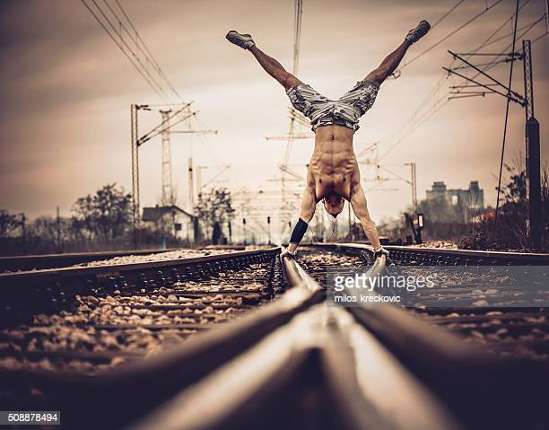 Hand stand on railroad tracks.