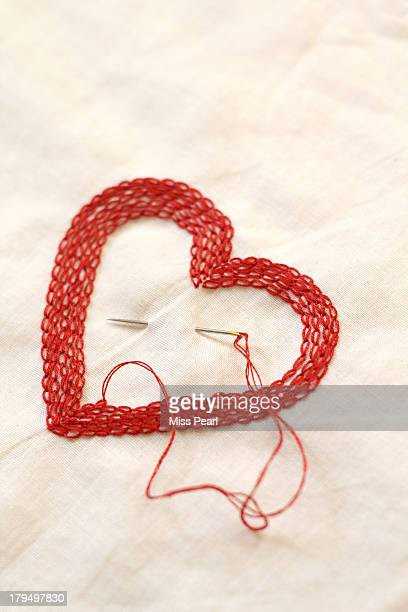 Hand stitch heart with needle and thread